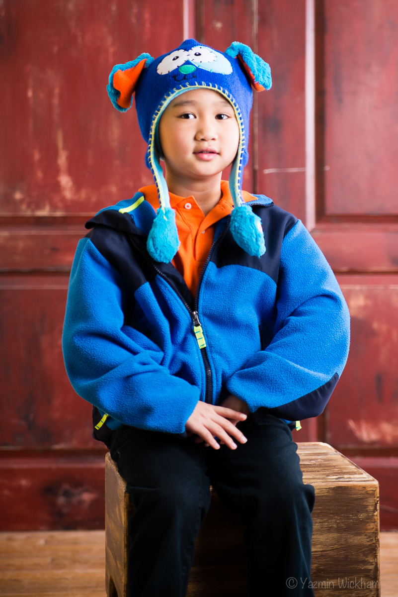 Boy sitting on box with winter hat - flash photography shot