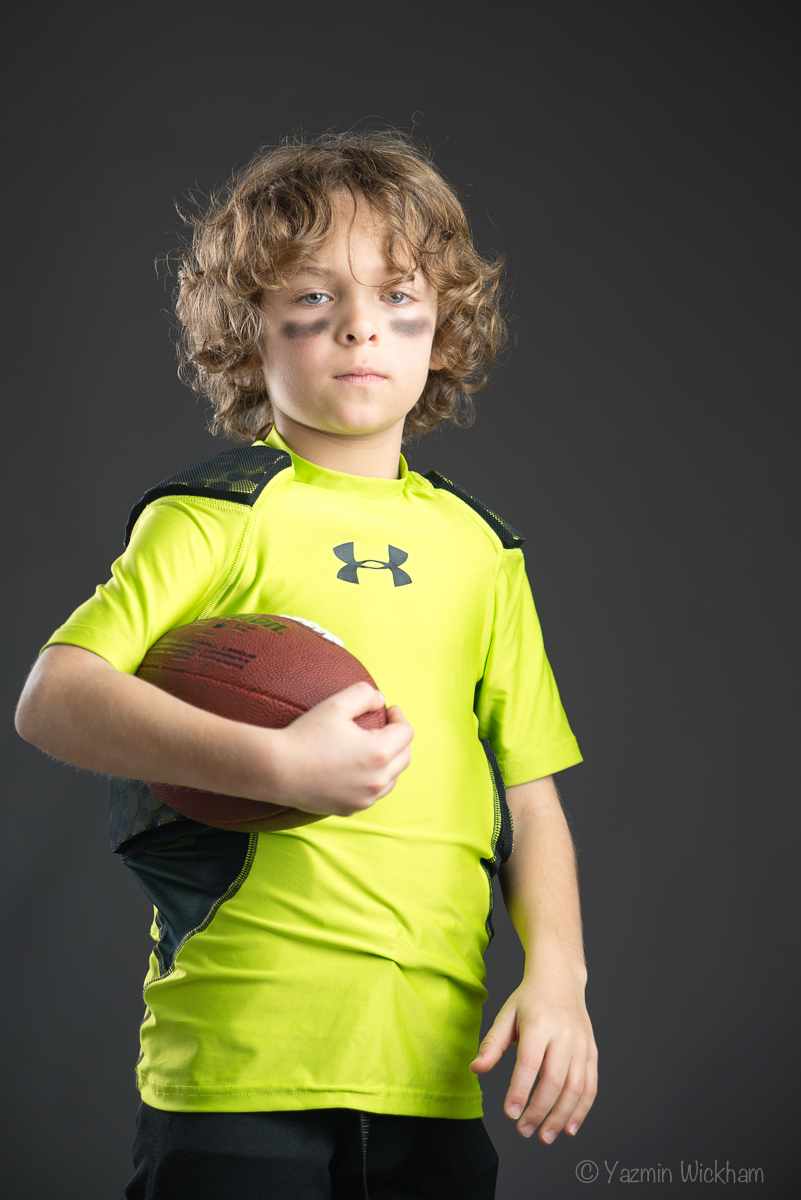 Boy in football uniform with football - flash photography shot